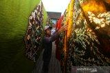 Pekerja menjemur kain sasirangan di rumah produksi kain Zahra Sasirangan di Sungai Jingah, Banjarmasin, Kalimantan Selatan, Sabtu (14/12/2019). Rumah produksi kain sasirangan tersebut, dalam sehari mampu memproduksi 50 lembar hingga 300 lembar kain sasirangan dengan harga Rp 65 ribu hingga Rp 250 ribu per lembar tergantung jenis kainnya. Foto Antaranews Kalsel/Bayu Pratama S.