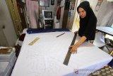 Pekerja membuat motif di kain di salah satu rumah produksi kain sasirangan di Sungai Jingah, Banjarmasin, Kalimantan Selatan, Sabtu (14/12/2019). Rumah produksi kain sasirangan tersebut, dalam sehari mampu memproduksi 50 lembar hingga 300 lembar kain sasirangan dengan harga Rp 65 ribu hingga Rp 250 ribu per lembar tergantung jenis kainnya. Foto Antaranews Kalsel/Bayu Pratama S.