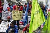 Massa  buruh yang tergabung dari sejumlah serikat pekerja melakukan aksi unjuk rasa di depan Gedung DPRD Jawa Barat, Bandung, Jawa Barat, Senin (23/12/2019).  Aksi tersebut untuk menuntut Gubernur Jawa Barat merevisi SK upah minimum kota/kabupaten tahun 2020 serta menolak revisi UU No 13 tahun 2003 tentang ketenagakerjaan. ANTARA JABAR/Novrian Arbi/agr