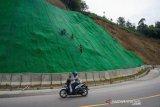 Pekerja memasang geogrid biaxial pada proyek rehabilitasi Jalan Trans Sulawesi