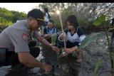 Anggota Polisi dan pelajar menanam bibit pohon bakau dalam program Polri Peduli Penghijauan di Tanjung Benoa, Badung, Bali, Jumat (10/1/2020). Kegiatan yang digelar serentak se-Indonesia tersebut untuk memperingati Hari Lingkungan Hidup Nasional dan Hari Gerakan sejuta Pohon Sedunia untuk kelestarian lingkungan. ANTARA FOTO/Nyoman Hendra Wibowo/nym