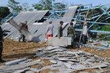 BERSIHKAN PUING BANGUNAN. Warga dibantu TNI membersihkan puing bangunan pasar yang ambruk akibat angin kencang di Desa Montok, Pamekasan, Jawa Timur, Sabtu (11/1/2020). Hujan lebat yang disertai angin kencang pada Jumat (10/1/2020) petang itu, menyebabkan 13 bangunan di Desa Montok dan Desa Lancar, rusak parah. Antara Jatim/Saiful Bahri/zk