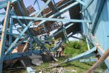 Warga membersihkan puing bangunan pasar yang ambruk akibat angin kencang di Desa Montok, Pamekasan, Jawa Timur, Sabtu (11/1/2020). Hujan lebat yang disertai angin kencang pada Jumat (10/1/2020) petang itu, menyebabkan 13 bangunan di Desa Montok dan Desa Lancar, rusak parah. Antara Jatim/Saiful Bahri/zk