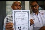 Nurdin Abdullah (64) Warga Aceh Timur, didampingi Ketua Yayasan Advokasi Rakyat Aceh (YARA) Safaruddin (kanan) memperlihatkan ijazah atas nama anaknya, Safridawati yang diduga korban perdagangan manusia, saat melapor di Mapolda Aceh, Banda Aceh, Senin (13/2/2020). Nurdin Abdullah bersama YARA berharap Polda Aceh dan Kedutaan Besar Indonesia di Malaysia dapat menemukan anaknya yang berangkat ke Malaysia sejak tahun 2015 dan diduga korban perdagangan manusia. ANTARA FOTO/Ampelsa/nym