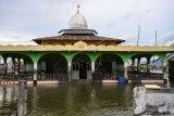 Seorang warga berada di dalam masjid yang berada di tengah genangan banjir rob atau banjir akibat air laut yang pasang di Desa Tompe, Kecamatan Sirenja, Kabupaten Donggala, Sulawesi Tengah, Minggu (12/1/2020). Banjir rob yang melanda permukiman warga itu disebabkan karena terjadinya penurunan permukaan tanah sedalam dua meter akibat gempa 7,4 SR yang berpusat di desa itu pada 28 September 2019. ANTARA FOTO/Basri Marzuki/aww.
