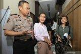 Kabid Humas Polda Jawa Timur Kombes Pol Trunoyudo Wisnu Andiko (kiri) mendampingi penyanyi Eka Deli (tengah) yang telah diperiksa sebagai saksi di Direktorat Reserse Kriminal Khusus (Ditreskrimsus) Polda Jawa Timur, Surabaya, Jawa Timur, Senin (13/1/2020). Eka Deli diperiksa sebagai saksi  selama sekitar sepuluh jam dengan 59 pertanyaan terkait kasus dugaan investasi ilegal 'MeMiles'. Antara Jatim/Didik/ZK