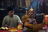 Perajin merangkai kertas emas (Kim Cua) di klenteng Hong Tiek Hian di Surabaya, Jawa Timur, Jumat (17/1/2020). Kertas emas yang dirangkai menjadi bentuk bunga Teratai, buah Nanas dan perahu Naga serta digunakan untuk upacara persembahyangan tersebut dijual dengan harga Rp5.000 - Rp1.200.000 tergantung bentuk dan tingkat kesulitan. Antara Jatim/Didik/ZK