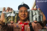 Pelajar menunjukkan uang logam rupiah untuk ditukarkan dengan uang kertas rupiah saat Peduli Koin Rupiah di Kantor Perwakilan Bank Indonesia Jawa Timur, Surabaya, Jawa Timur, Minggu (19/1/2020). Dalam kegiatan Peduli Koin Rupiah tersebut, Kantor Perwakilan Bank Indonesia Jawa Timur bersama 20 perbankan menyediakan layanan penukaran uang logam rupiah dengan modal yang telah disiapkan sebesar Rp1,75 Milyar. Antara Jatim/Didik/ZK