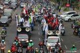 Ratusan buruh yang akan berunjuk rasa di DPRD Jawa timur melintas di Jalan Embong Malang, Surabaya, Jawa Timur, Senin (20/1/2020). Mereka menyerukan sejumlah aspirasi salah satunya menolak omnibus law ketenagakerjaan. Antara Jatim/Didik/ZK