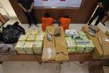 Dua orang tersangka dan barang bukti dihadirkan saat konferensi pers pengungkapan pengiriman narkoba jaringan internasional Malaysia-Sumatera-Jakarta, di Bareskrim Polri, Jakarta, Selasa (21/1/2020). Pengiriman narkoba jenis sabu sebanyak 70 kg tersebut menggunakan modus pengiriman dalam kemasan kopi dan ikan asin untuk mengelabuhi petugas. ANTARA FOTO/Reno Esnir/foc.