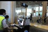 Petugas memantau suhu tubuh penumpang menggunakan alat pemindai suhu tubuh di Terminal Kedatangan Internasional Bandara Internasional I Gusti Ngurah Rai, Bali, Rabu (22/1/2020). Alat pemindai suhu tubuh tersebut dipasang Kantor Kesehatan Pelabuhan (KKP) Kelas I Denpasar sebagai upaya pengawasan dan antisipasi penyebaran Virus Corona yang mewabah dari Wuhan, China. ANTARA FOTO/Fikri Yusuf/nym