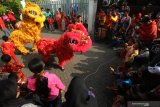 Warga menyaksikan atraksi Barongsai di kampung pecinan Tambak Bayan, Surabaya, Jawa Timur, Sabtu (25/1/2020). Peragaan busana pakaian tradisional tiongkok dan atraksi Barongsai meramaikan perayaan tahun baru Imlek 2571 di kampung itu. Antara Jatim/Didik/Zk