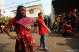 Warga menyaksikan peragaan busana di kampung pecinan Tambak Bayan, Surabaya, Jawa Timur, Sabtu (25/1/2020). Peragaan busana pakaian tradisional tiongkok dan atraksi Barongsai meramaikan perayaan tahun baru Imlek 2571 di kampung itu. Antara Jatim/Didik/Zk