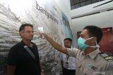 Petugas Kantor Kesehatan Pelabuhan (KKP) memeriksa penumpang yang baru tiba dengan alat deteksi suhu tubuh (thermoscan) di terminal kedatangan bandara Internasional Banyuwangi, Jawa Timur, Senin (27/1/2020). Pemeriksaan  untuk mengantisipasi penyebaran virus corona itu, dilakukan karena Banyuwangi menjadi tempat wisata yang banyak dikunjungi wisatawan lokal dan internasional melalui Bandara. Antara Jatim/Budi Candra Setya/zk.