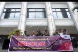 Belasan warga yang tergabung dalam Forum Masyarakat Minangkabau (FMM) menggelar spanduk yang berisikan menolak kedatangan turis China, saat mengadakan audensi di kantor Dewan Perwakilan Daerah Sumatera Barat, Padang, Senin (27/1/2020). Forum Masyarakat Minangkabau mendesak pemerintah setempat untuk memulangkan kembali 150 orang wisatawan dari China melalui agen travel Coco's Tour dan PT Marawa Coporate, yang datang pada Minggu (26/1/2020), melalui Bandara International Minangkabau (BIM), terkait berkembangnya wabah virus Corona. ANTARA FOTO/Muhammad Arif Pribadi/nym