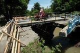 Melintasi jembatan rusak