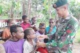 Prajurit TNI mengajak anak-anak Kampung Kondo minum susu