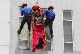 SIMULASI PENANGANAN BENCANA KEBAKARAN GEDUNG. Petugas Pemadam Kebakaran  berusaha mengevakuasi korban dari ketinggian dalam Simulasi Penanganan Bencana Kebakaran Gedung di Malang, Jawa Timur, Senin (27/1/2020). Simulasi tersebut bertujuan melatih kesiapan dan koordinasi anggota Pemadam Kebakaran, SAR, Polisi dan TNI dalam menangani bencana kebakaran di gedung tinggi. Antara Jatim/Ari Bowo Sucipto/zk