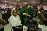Romo RD Thomas Agustinus Wibowo mengoleskan minyak suci kepada salah satu jemaat saat mengikuti Misa Hari Orang Sakit Sedunia yang ke-28 di Gereja Santa Maria Tak Bercela (SMTB), Surabaya, Jawa Timur, Selasa (11/2/2020). Misa yang diikuti sekitar 300 pasien dan lansia tersebut mengusung tema