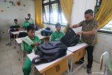 Petugas dari Dinas Pendidikan Kota Surabaya memeriksa barang bawaan pelajar saat melakukan sidak di SMP Negeri 11, Surabaya, Jawa Timur, Kamis (13/2/2020). Sidak tersebut dilakukan sebagai tindakan pencegahan untuk menekan kenakalan dan perbuatan yang mempengaruhi sikap dan mental pelajar. Antara Jatim/Moch Asim/zk.