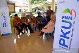 PIC Pengembangan Kapasitas Usaha (PKU) PT Permodalan Nasional Madani Cabang Surabaya, Dicky Irwanto (kedua kanan), Regional Manager Mekaar Istiqomah (ketiga kiri), staff divisi PKU PNM, Intan (kedua kiri), Kepala Cabang PNM Driyorejo, Dian Mirta Susanti (ketiga kanan) dan Camat Balongpanggang, M Jusuf Asyori (kiri) berbincang dengan nasabah program Membina Ekonomi Keluarga Sejahtera (Mekaar) di kantor Kecamatan Balongpanggang, Kabupaten Gresik, Jawa Timur, Jumat (14/2/2020). Kegiatan yang diikuti ratusan nasabah tersebut digelar sebagai upaya meningkatkan semangat para nasabah PNM Mekaar untuk mengembangkan usahanya. Antara Jatim/Syaiful Arif/zk