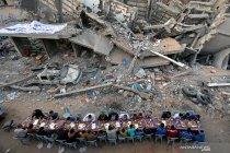Warga Palestina berbuka puasa di lokasi bekas serangan udara Israel