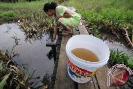Warga transmigrasi Pulau Maya minum air parit