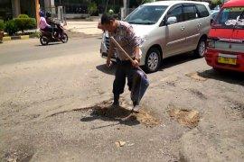 Anggota Satlantas Polres Cilegon Uruk Jalan Berlubang
