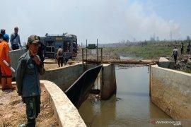 Water flows from Riam Kanan dam to wet burning land around Syamsudin Noor Airport