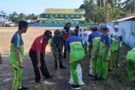 Anggota TNI bersama warga  bersihkan Pasar Muara Uya