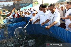 Banjar Regent and santri harvest lele