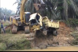 Truk bermuatan sawit terseret arus, supir selamat berenang ke tepi sungai