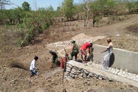Prajurit Yonif 142/KJ bersama warga bangun bendungan irigasi