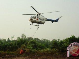 Helikopter Bolkow BO-105 dari Badan Nasional Penanggulangan Bencana (BNPB) mengambil air dari kanal untuk memadamkan kebakaran lahan gambut, di perkebunan sawit di Kecamatan Terentang, Kabupaten Kubu Raya, Kalbar, Rabu (21/10). Pemprov Kalbar bersama BNPB melaksanakan operasi pemadaman api dengan menggunakan Helikopter Bolkow BO-105 untuk menjatuhkan bom air (water bombing) guna memadamkan 154 titik api akibat kebakaran lahan yang terjadi di Kabupaten Kubu Raya, Kayong Utara dan Ketapang. ANTARA FOTO/Jessica Helena Wuysang/15