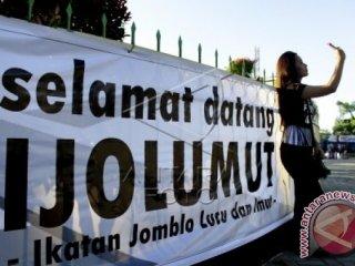 Remaja berswafoto di depan spanduk selamat datang pada Festival Jomblo Anti Korupsi di Taman Kota Gorontalo, Gorontalo, Minggu (14/2). Festival yang digelar Pusat Studi Kebijakan dan Anti Korupsi Universitas Negeri Gorontalo (UNG) dan Gorontalo Unite tersebut bertekad untuk membebaskan Indonesia dari korupsi guna mewujudkan Indonesia yang adil dan beradab sesuai dengan Pancasila dan UUD 45. ANTARA FOTO/Adiwinata Solihin.