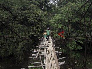 Warga melintasi jembatan gantung bambu yang rusak di Pondok Rajeg, Bogor, Jawa Barat, Selasa (25/9). Jembatan gantung penghubung desa Panjang Pondok Rajeg dan desa Utan Citayam tersebut sudah rusak dan lapuk sehingga dapat membahayakan warga yang melintas. ANTARA JABAR/Yulius Satria Wijaya/agr/18.