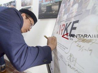 Ketua Organisasi Internasional Alumni Al Azhar (OIAA) Tuan Guru Bajang (TGB) Zainul Majdi menandatangani poster pameran foto ARKE kilas balik Jabar di Galeri Foto Antara Jabar, Bandung, Jawa Barat, Sabtu (26/1/2019). Kunjungan TGB Zainul Majdi tersebut dilakukan dalam rangka mengapresiasi karya foto pewarta Antara Jawa Barat. ANTARA JABAR/Raisan Al Farisi/agr.