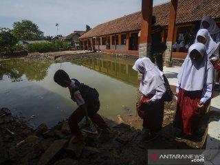 Siswa berjalan keluar kelas seusai mengikuti  Ujian Sekolah Berstandar Nasional (USBN) di SDN VII Dayeuhkolot yang terdampak banjir di Kabupaten Bandung, Jawa Barat, Senin (22/4/2019). Sebanyak 35 siswa mengikuti USBN pascabanjir yang melanda kawasan tersebut. ANTARA JABAR/Raisan Al Farisi/agr