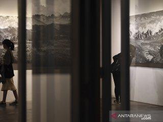 Pengunjung melihat pameran foto tunggal karya Deden Hendan Durahman di Galeri Orbital Dago, Bandung, Jawa Barat, Minggu (16/6/2019). Pameran yang bertema Look After ini merefleksikan makna kebenaran dalam bayang-bayang kebohongan di era