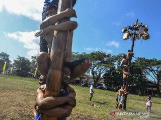 Warga mengikuti lomba panjat pinang pada Pesta Rakyat HUT ke-73 Bhayangkara di Lapangan Dadaha, Kota Tasikmalaya, Jawa Barat, Rabu (10/7/2019). Perlombaan panjat pinang, bakiak, makan kerupuk, dan balap karung antar warga dan Bhabinkamtibmas Polres Tasikmalaya Kota dalam rangka memeriahkan puncak HUT Bhayangkara sekaligus mempererat sinergitas antara Polri dan masyarakat dalam menjaga keamanan dan ketertiban. ANTARA JABAR/Adeng Bustomi/agr