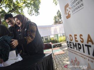 Direktur Group Manajemen Risiko Lembaga LPS Dewi Gayatri (kanan) mendampingi anak-anak saat menimbang berat badan seusai peresmian Desa GEMPITA (Gerakan Menu Empat Bintang) di Bandung, Jawa Barat, Kamis (18/7/2019). Kegiatan tersebut bertujuan untuk pencegahan dan penanggulangan stunting melalui pemberian makanan tambahan harian selama enam bulan kepada balita dan ibu hamil yang membutuhkan dan edukasi kesehatan secara umum, serta program pengembangan posyandu. ANTARA JABAR/M Agung Rajasa/agr