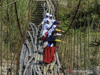 Siswa Sekolah Dasar (SD) menyeberangi Jembatan Gantung Cipangarangan, Desa Lengkongjaya yang melintasi Sungai Ciwulan, Kabupaten Tasikmalaya, Jawa Barat, Selasa (23/7/2019). Jembatan penghubung kecamatan Salawu dengan Kecamatan Cigalotang tersebut rusak parah, tetapi warga terpaksa melintasi karena menjadi akses utama dari Kampung Cibaeud dan sekitarnya. ANTARA JABAR/Adeng Bustomi/agr