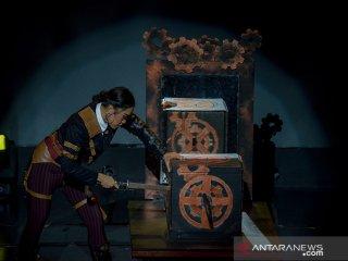 Seorang pesulap memasukan pedang kedalam kotak yang berisikan manusia saat pertunjukan Cadabra dengan tema