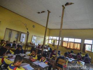 Siswa mengikuti kegiatan belajar mengajar didalam kelas yang rusak di SDN Pasirhuni 2, Kampung Cipaheuteun, Kabupaten Tasikmalaya, Jawa Barat, Kamis (19/9/2019). Bangunan ruang kelas empat tersebut rusak sejak dua tahun lalu akibat dimakan usai, sehingga pihak sekolah menopang atap flafonnya menggunakan bambu dan hingga kini belum mendapat perhatian dari pemerintah setempat. ANTARA FOTO/Adeng Bustomi/agr