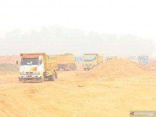 Sejumlah truk melintasi lokasi proyek pembangunan Terminal Kijing yang diselimuti kabut asap di Kabupaten Mempawah, Kalimantan Barat, Kamis (19/9/2019). General Manager Cabang Pontianak PT Pelindo II (Persero)/IPC Adi Sugiri menyatakan kemajuan dari tahap pertama pembangunan Terminal Kijing yang merupakan pelabuhan berstandar internasional terbesar di Kalimantan tersebut mencapai 23 persen dan ditargetkan pada pertengahan 2020 sudah beroperasi. ANTARA FOTO/Jessica Helena Wuysang
