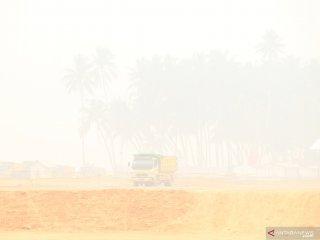 Sebuah truk melintasi lokasi proyek pembangunan Terminal Kijing yang diselimuti kabut asap di Kabupaten Mempawah, Kalimantan Barat, Kamis (19/9/2019). General Manager Cabang Pontianak PT Pelindo II (Persero)/IPC Adi Sugiri menyatakan kemajuan dari tahap pertama pembangunan Terminal Kijing yang merupakan pelabuhan berstandar internasional terbesar di Kalimantan tersebut mencapai 23 persen dan ditargetkan pada pertengahan 2020 sudah beroperasi. ANTARA FOTO/Jessica Helena Wuysang