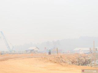 Seorang pekerja melintasi lokasi proyek pembangunan Terminal Kijing yang diselimuti kabut asap pekat di Kabupaten Mempawah, Kalimantan Barat, Kamis (19/9/2019). General Manager Cabang Pontianak PT Pelindo II (Persero)/IPC Adi Sugiri menyatakan kemajuan dari tahap pertama pembangunan Terminal Kijing yang merupakan pelabuhan berstandar internasional terbesar di Kalimantan tersebut mencapai 23 persen dan ditargetkan sudah beroperasi pada pertengahan 2020. ANTARA FOTO/Jessica Helena Wuysang.