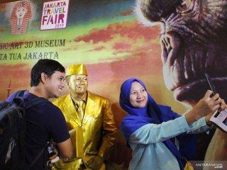 Dua pengunjung mall berfoto dengan manusia patung emas di acara Jakarta Travel Fair 2019 di Pontianak, Kalimantan Barat, Minggu (29/9/2019). Jakarta Travel Fair 2019 yang setiap tahun diadakan Dinas Pariwisata provinsi DKI Jakarta tersebut bertujuan mempromosikan sejumlah destinasi wisata di Jakarta kepada masyarakat Pontianak. ANTARA FOTO/Jessica Helena WuysangANTARA FOTO/JESSICA HELENA WUYSANG (ANTARA FOTO/JESSICA HELENA WUYSANG)