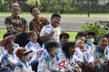 Presiden Joko Widodo (kiri) didampingi Ibu Negara Iriana Joko Widodo dan anak-anak penderita kanker pendampingan Yayasan Kanker Anak Indonesia tertawa saat menyaksikan pertunjukan sulap disela-sela silaturahmi di halaman belakang Istana Bogor, Jawa Barat, Jumat (6/4). Yayasan Kanker Anak Indonesia dalam kesempatan tersebut meminta regulasi impor obat kanker dipermudah dan bea masuk ditiadakan. ANTARA FOTO/Puspa Perwitasari/wdy/2018