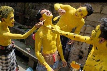 Sejumlah remaja mengecat tubuhnya menjelang berkeliling kampung dalam tradisi Ngerebeg di Desa Tegallalang, Gianyar, Bali, Rabu (28/8/2019). Tradisi ngerebeg tersebut merupakan rangkaian upacara persembahyangan di Pura Duur Bingin Desa Tegallalang yang digelar setiap enam bulan sekali untuk memohon keselamatan dan ritual tolak bala. ANTARA FOTO/Nyoman Hendra Wibowo/nym.